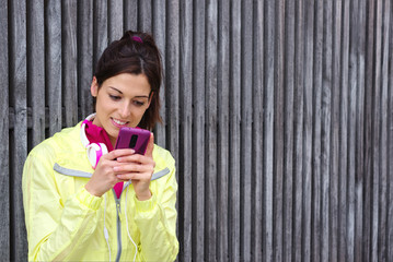 Female athlete texting message on smartphone