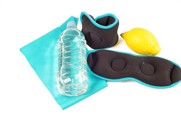 Ankle weights, band, lemon and bottle with water, isolated