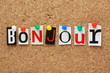 The word Bonjour on a cork notice board