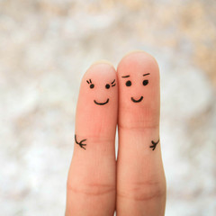 Happy couple. A man and a woman hug. Finger smileys.