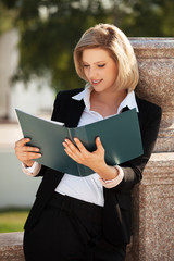 Happy young business woman with a folder outdoor