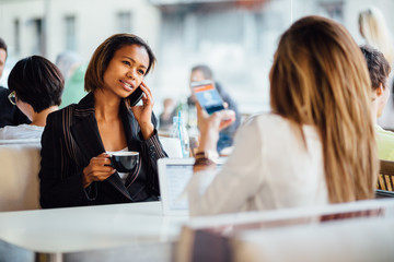 Multi ethnic businesswomen talking on phone in coffee shop