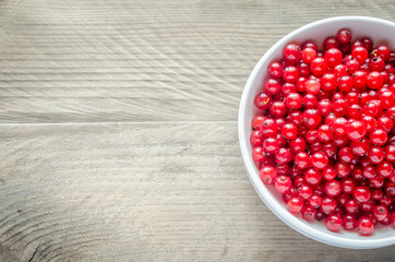 Bowl with fresh redcurrant on the wooden table