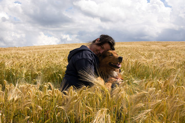 Frau mit Hund im Weizenfeld