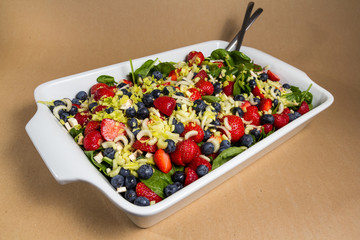 Mixed salad of the summer with fruit in a dish
