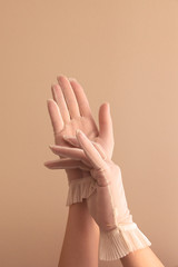 female hands adjusting vintage sheer gloves