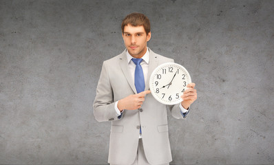 handsome businessman pointing finger to wall clock