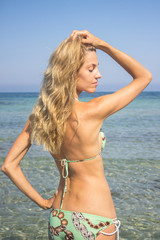 Beautiful blonde woman sunbathing standing in sea water, torso