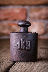 Vintage iron 1 kg weight in front of an old brick wall.