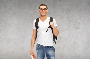 smiling student with backpack and book