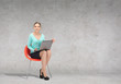 young businesswoman sitting in chair with laptop