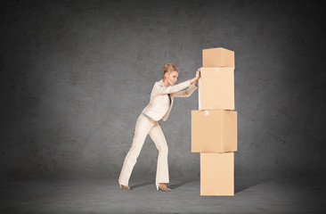 businesswoman pushing tower of cardboard boxes