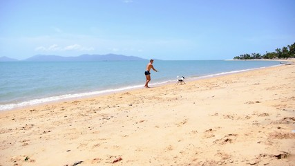 Tanned Man and Cute Dog Playing on Seacoast in Thailand.