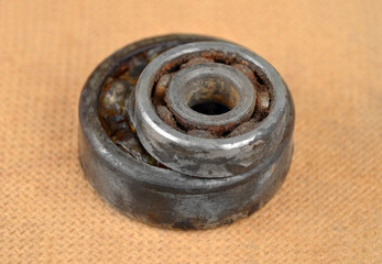 Old and rusty ball bearing on wooden background