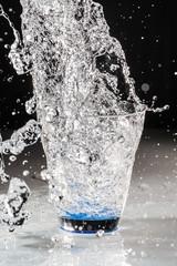 Versamento acqua nel bicchiere in  trasparenza
