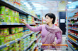 woman pushing shopping cart choosing at goods in supermarket