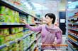 woman pushing shopping cart choosing at goods in supermarket