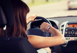 woman driving a car and looking at watch