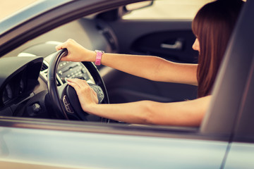 woman driving a car with hand on horn button
