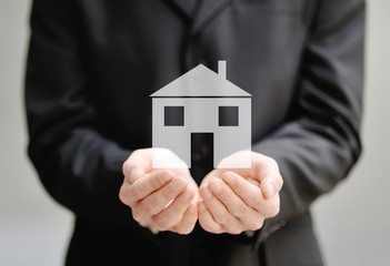 hands of a man holding a house, insurance and protection concept