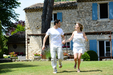 happy young man woman couple fun running in meadow grass