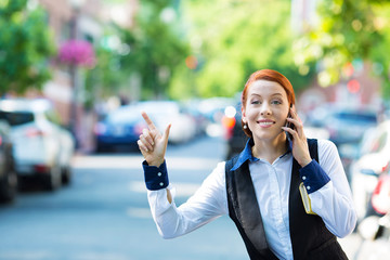 Young business woman talking on smartphone, hails taxi cab