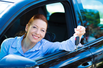 Happy young woman showing keys from her new car
