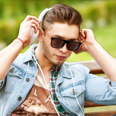 handsome fashion man listening to music on the grass in the park