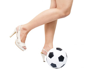 Woman feet kick the ball by high hill