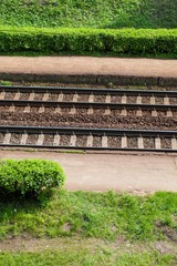 railroad tracks on the background of green grass in summer