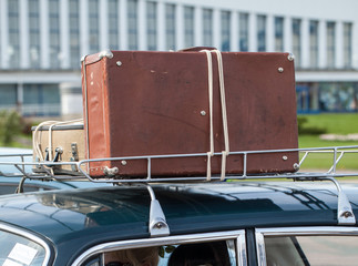 old suitcases tied to the roof rack of car