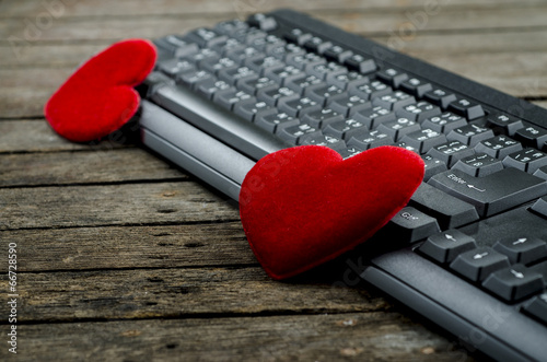 Red heart and Computer Keyboard on wooden