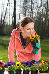 Woman smelling pansy flowers in pot