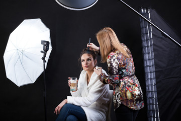 Make-up artist preparing female model for photo shoot