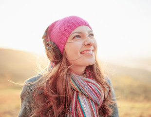 Young woman enjoying a music in the fall season. Autumn outdoor