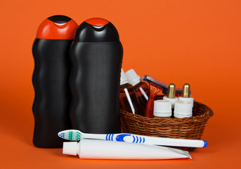 Shampoo, gel, cosmetics in basket and toothbrush