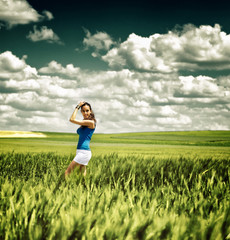 Pretty young girl in a field under a dramatic sky