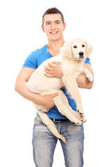 Smiling young man holding a dog