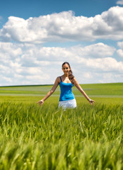 Happy carefree young woman in a green wheat field
