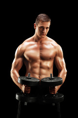 Muscular young man exercising with barbells on black background