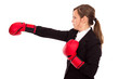 Businesswoman with boxing gloves punching and hitting standing i