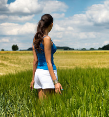 Trendy young woman standing in a green field
