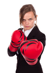 Young businesswoman wearing boxing gloves ready for the competit
