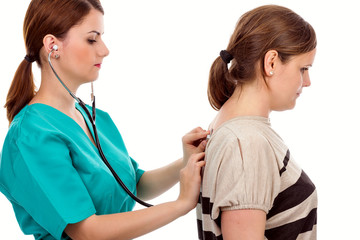 Young doctor examining lungs of  patient with stethoscope