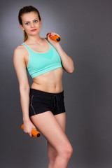 Young attractive woman working out with dumbbells