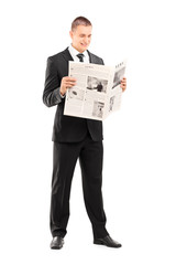 Young businessman reading a newspaper