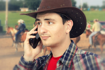Slightly perplexed cowboy talking on phone