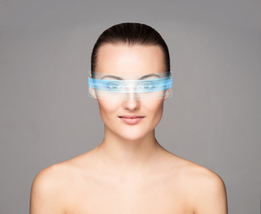 Portrait of a beautiful and young woman in techno glasses