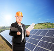 Female architect standing next to solar panels