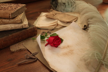 Red rose and beautiful quill on a vintage desk